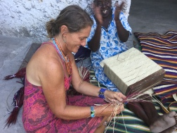 Mzungu tries some weaving. The aunt gets a kick out of it!