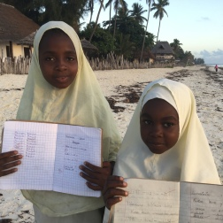 Sweet Muslim school girls proud of their work stopping to talk on their way to school. They all wanted pencils and books. Next time!